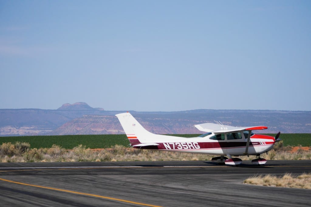 The Bears Ears can be seen in the background as participants prepare to depart the Blanding airport for an overflight of the area.